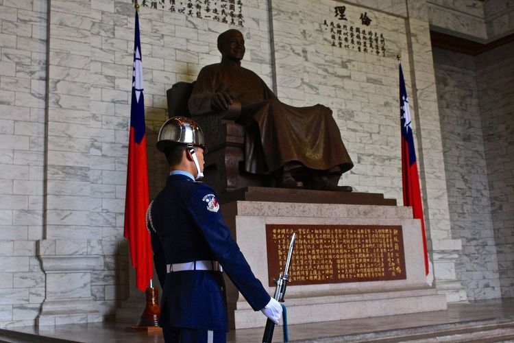 Security Guard Standing By Statue In Historic Building