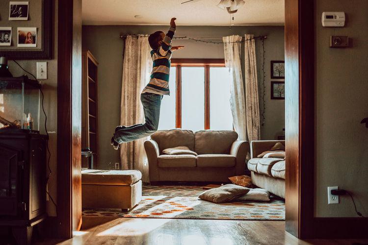 Woman jumping on sofa at home