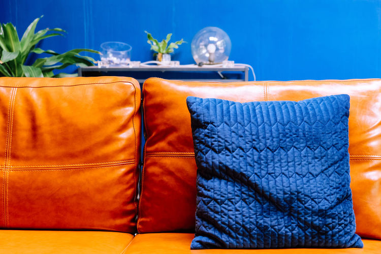 Close up detail of blue pillow on leather sofa Decor Leather Living Orange Pillow Bag Blue Blue Background Brown Close-up Container Cushion Decoration Decorations Decorative Food And Drink Furniture Furniture Details Group Of Objects Home Interior Household Equipment Indoors  Interior Design Leather Sofa Living Room Nature No People Orange Color Pattern Personal Accessory Plant Potted Plant Sofa Still Life Table Tablecloth Textile Transparent