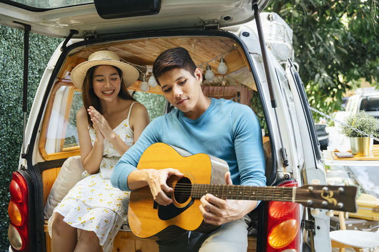 Young man playing guitar sitting with woman in car trunk