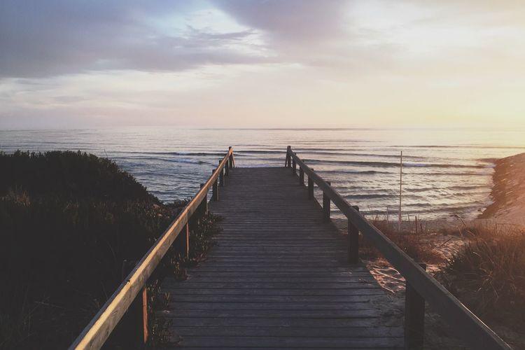 Boardwalk on sea against sky during sunset