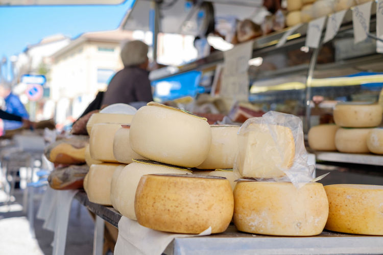 cheese on market in Italy Business Cheese Choice Dairy Product Day Focus On Foreground Food Food And Drink For Sale Freshness Healthy Eating Incidental People Large Group Of Objects Market Market Stall One Person Retail  Retail Display Stack Wellbeing