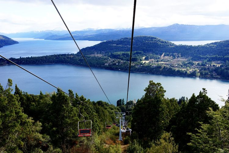 High Angle View Of Ski Lifts Over Forest And River Against Sky