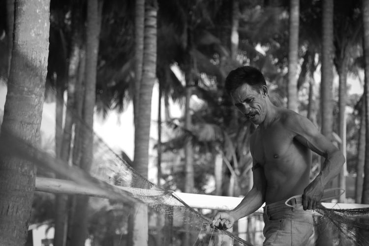 Shirtless man holding fishing net while standing against trees
