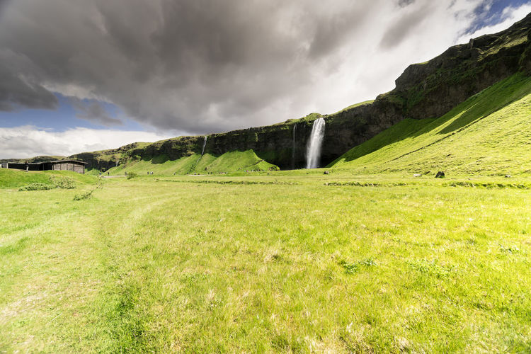 Unrecognizable tourists occupy the path leading towrads the waterfall Seljalandsfoss, one of the stops on Iceland's popular tourist route the golden circle. Iceland Travel Beauty In Nature Cloud - Sky Day Environment Europe Field Grass Green Color Idyllic Landscape Mountain Nature No People Non-urban Scene Outdoors Plant Rolling Landscape Scenics - Nature Selfoss Seljalandsfoss Sky Tranquil Scene Tranquility