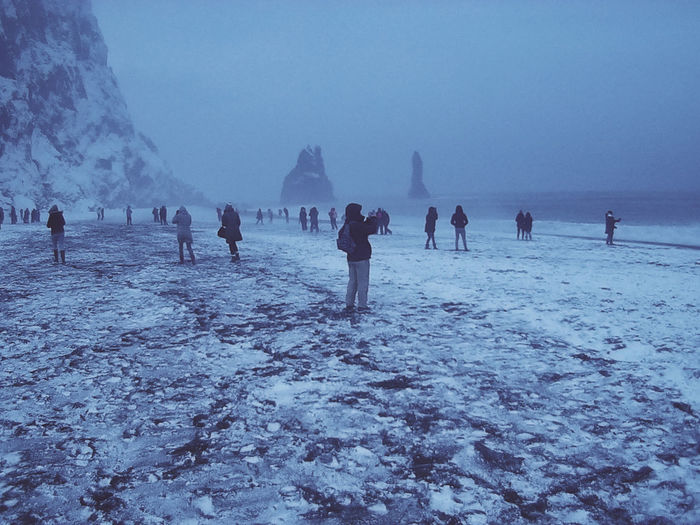People on snow covered land against sky