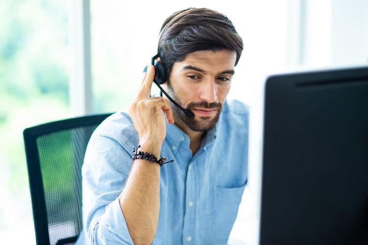 Businessman talking through headset in office