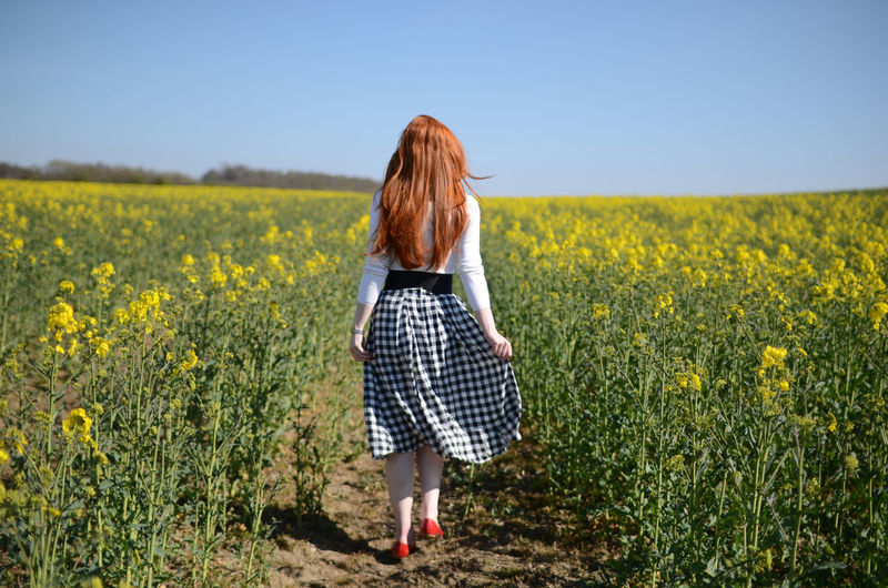 Full Length Rear View Of Woman Walking In Agricultural Field Against Clear Sky