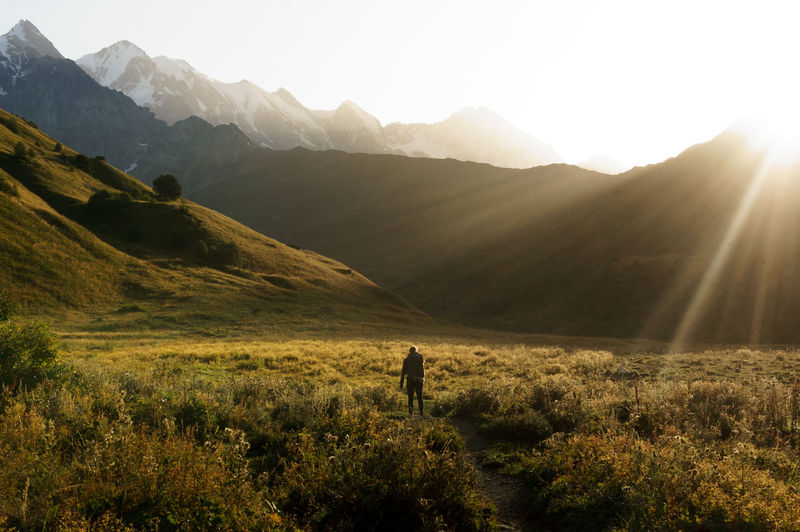 Walking to Ushguli from Mestia at dawn. Beauty In Nature Bright Environment Land Landscape Leisure Activity Lens Flare Lifestyles Mountain Mountain Range Nature Non-urban Scene One Person Outdoors Plant Real People Scenics - Nature Sky Sun Sunbeam Sunlight Tranquil Scene Tranquility