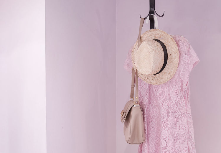 Dress with hat and purse hanging on coat hook against pink wall