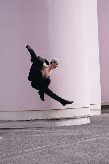 Side view of woman jumping against wall