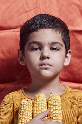Close-up portrait of boy standing against wall