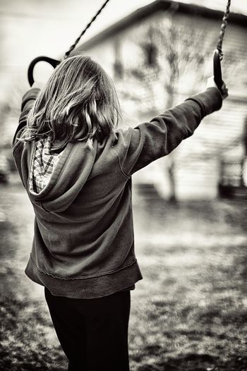 Teenage girl holding gymnastic rings while standing outdoors