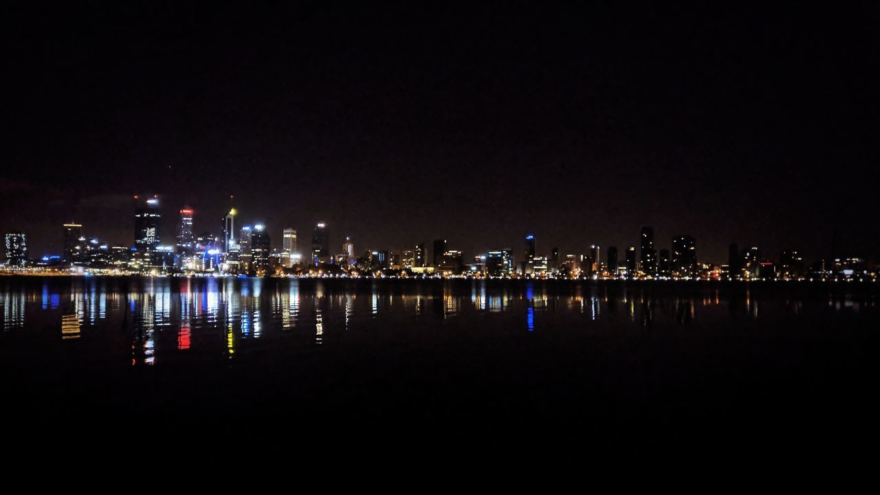 night, illuminated, architecture, city, built structure, building exterior, travel destinations, outdoors, city life, skyscraper, river, waterfront, water, urban skyline, cityscape, no people, clear sky, sky