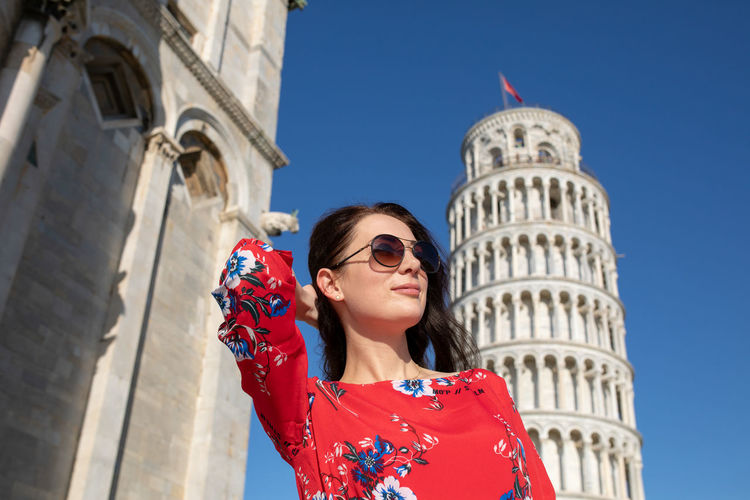 Woman with hand in hair standing against leaning tower of pisa in italy