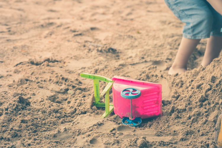 Low section of boy playing with toy on sand