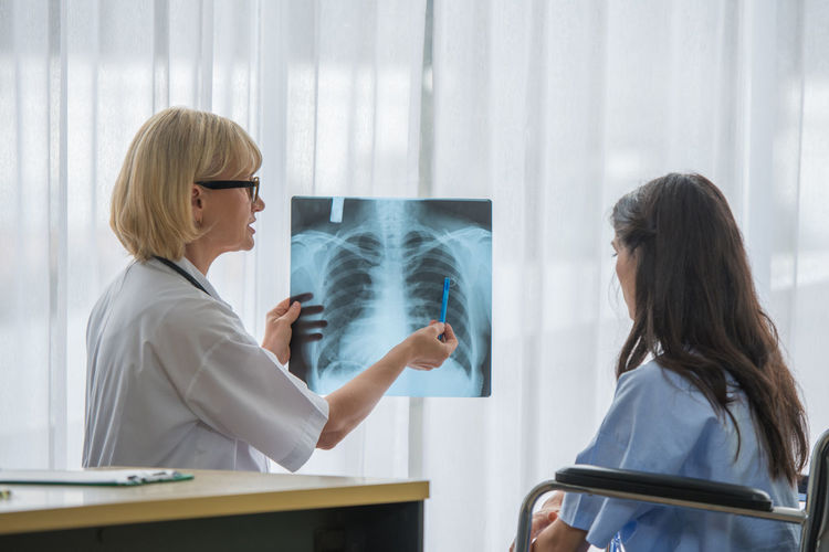 Female doctor showing x-ray to patient in hospital