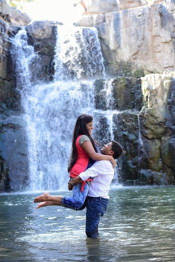 Full Length Of Young Man Lifting Woman While Standing Against Waterfall At River