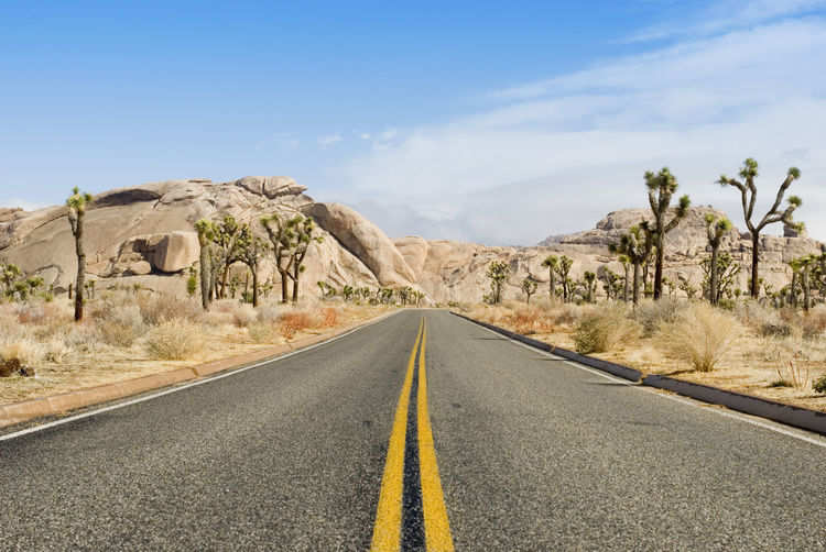 a road through the joshua tree national park, california Asphalt Blue Sky Cliffs Clouds Desert Drive Joshua Tree Lines National Park Perspective Perspective Photography Perspectives Road Route Stone Tarmac Vanishing Point