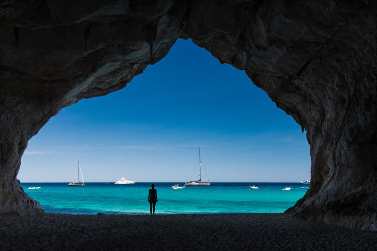 Silhouette Woman Standing In Cave At Beach Against Sea And Sky