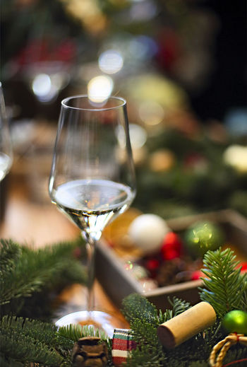 Close-up of wine glass on table against christmas tree