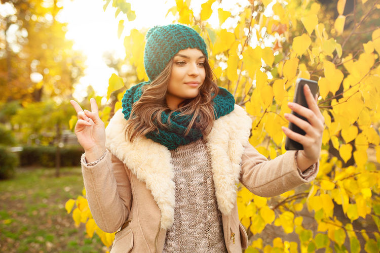 Young woman in warm clothing taking selfie through smart phone while showing peace sign against autumn tree