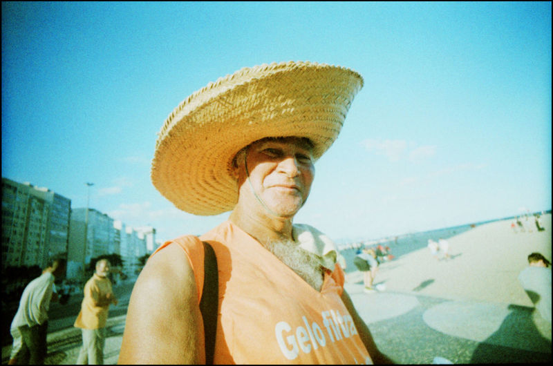 Portrait of man wearing hat against sky in city