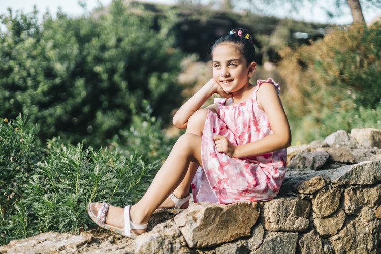 Cute girl sitting on rock