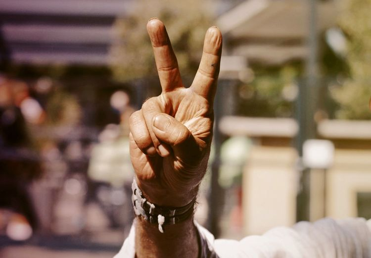 Cropped hand of man showing peace sign