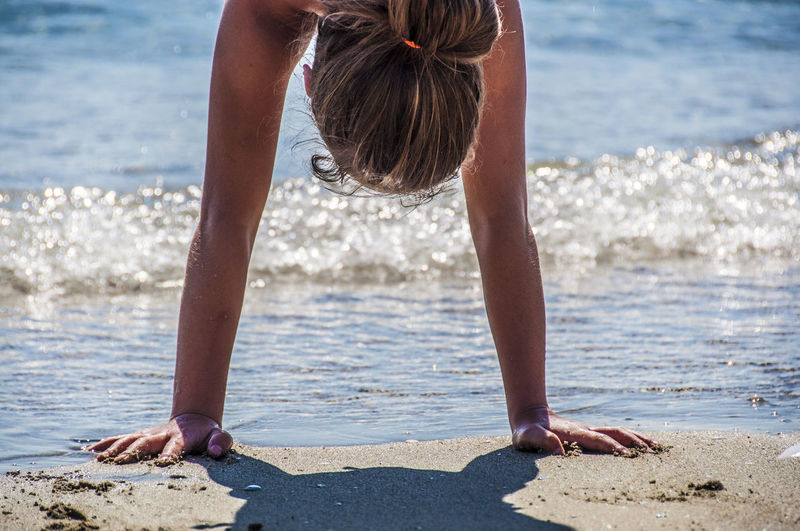 Close-Up Of Woman Doing Handstand On Shore At Beach