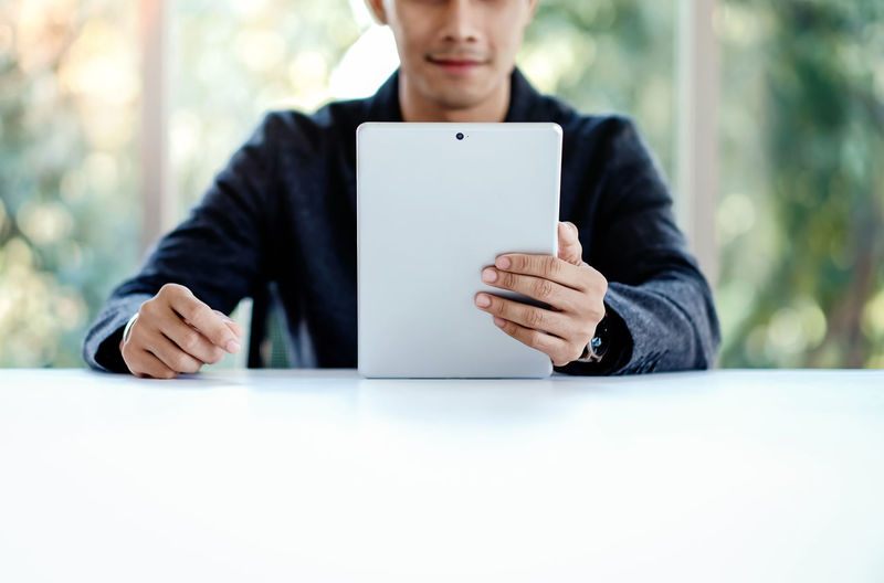 Businessman Working on Digital Tablet in Office. Sitting at the Desk. Selective Focus on Device One Person Sitting Front View Holding Midsection Technology Digital Tablet Communication Wireless Technology Connection Real People Table Adult Leisure Activity Day Lifestyles Indoors  Concentration Blank Businessman Asian  Desk Tablet