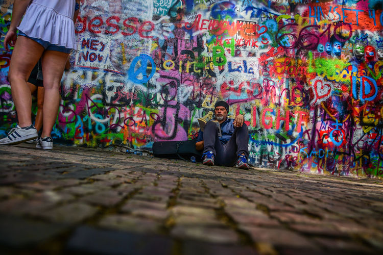Adult Art And Craft City Creativity Day Footpath Graffiti Leisure Activity Lifestyles Men Multi Colored People Real People Selective Focus Street Togetherness Wall - Building Feature Women
