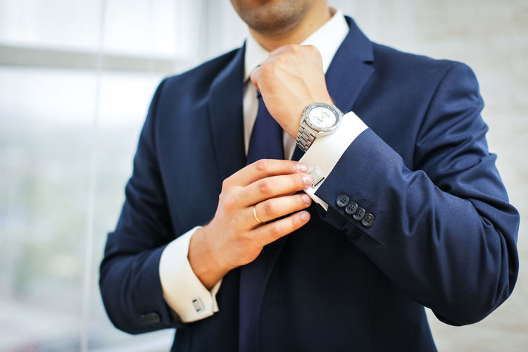 Midsection of businessman cuff link shirt sleeve at home