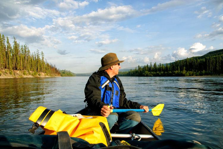 Man In Canoe On Yukon River Against Sky