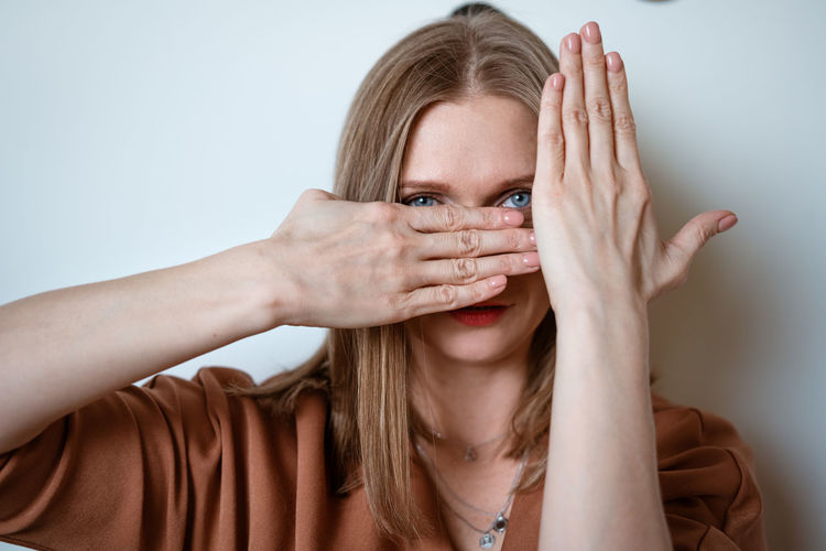 Woman covers her face with her hands