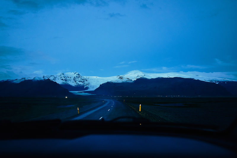 Cars on road by snowcapped mountains against sky seen through car windshield