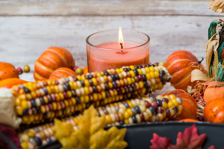 Indian corn in front of a candle with other decorations for fall Autumn Candle Halloween October Pumpkins Decoration Fall Home Decor Indian Corn Scarecrow Wooden