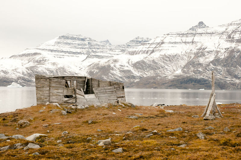 Broken Wooden Cabin By Lake Against Mountains