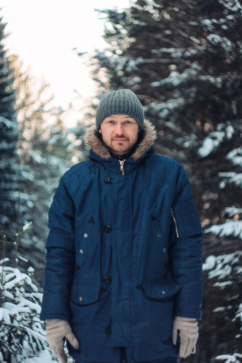 Portrait Of Man Wearing Warm Clothing While Standing Against Trees During Winter