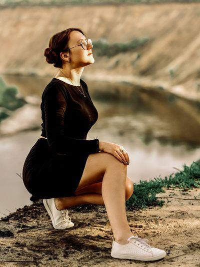 Woman looking away while sitting on land