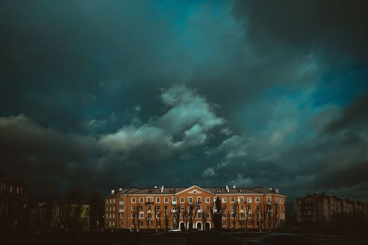 Low angle view of building against storm clouds