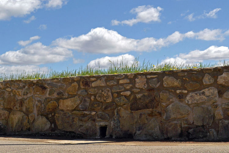 the blue sky beyond the stone wall Stone Wall Grass Sky Clouds And Sky Cloud - Sky Blue Stumbling Stumbling Block Barrier Closer Wall Sunlight Outdoors Solid Surrounding Wall