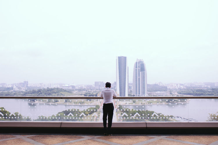 Rear view of man standing on railing against river