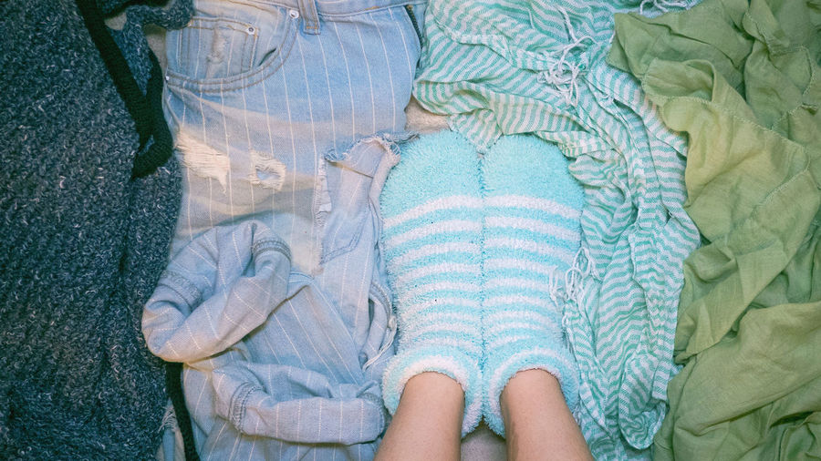 Low section of person wearing blue socks on bed