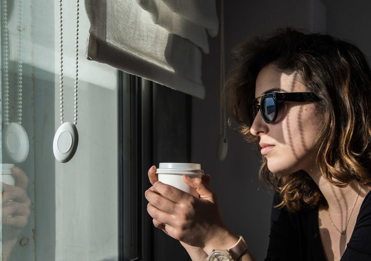 Casual Clothing Cup Of Coffee Eyeglasses  Front View Headshot Leisure Activity Lifestyles Mid Adult Mobile Phone Person Photography Themes Portrait Smart Phone Sunglasses The Portraitist - 2016 EyeEm Awards Thinking Wireless Technology Young Adult Young Women Natural Light Portrait