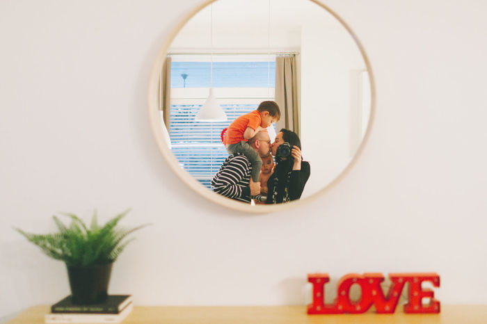 Reflection of family in mirror at home