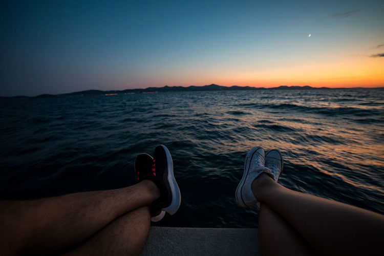 Low section of person relaxing on sea against sky during sunset