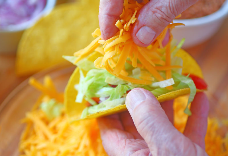 Man adds cheese to tacos Fingers Food Preparation Grated Cheese Green Hands Holding Home Cooking Home Food Homemade Food Indoors  Making Tacos Man Mexican Food Natural Light Older Person Overhead Point Of View Senior Shredded Lettuce Studio Shot Taco Night Taco Shells Textures Yellow