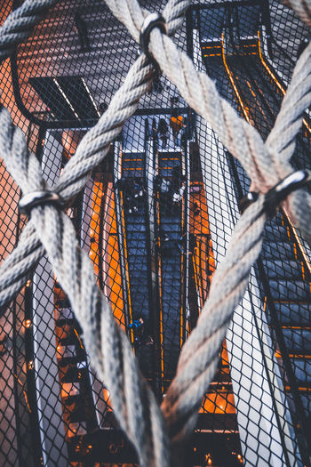 Low angle view of ropes hanging on metal fence