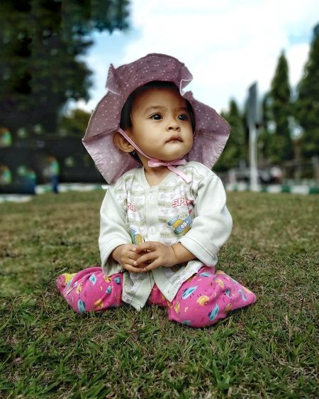 Cute Baby Girl Sitting On Grass In Field
